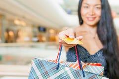 Zakończenie azjatykcia kobiety ręka trzyma kredytową kartę i torby Obraz Royalty Free