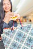 Zakończenie azjatykcia kobiety ręka trzyma kredytową kartę i torby Zdjęcie Royalty Free