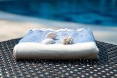 Zakończenie błękitny i biały Turecki ręcznik na rattan lounger z błękitnym pływackim basenem jako tło Obraz Stock