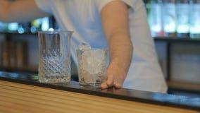 Zakończenie - barman stawia lód w szkło i miesza je z łyżką zdjęcie wideo