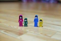 Zakończenie barwić drewniane figurki rodzina z dwa dziećmi na drewnianym podłogowym tle ojciec z córką, macierzysty w obraz royalty free
