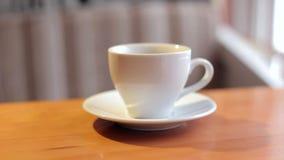 Zakończenie biała filiżanka kawy na stole w kawiarni zbiory wideo