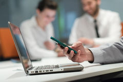 Zakończenie biznesmen up wręcza używać mądrze telefon na spotkaniu Obrazy Royalty Free