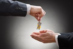 Zakończenie biznesmena ręka daje domu kluczowi Obraz Royalty Free