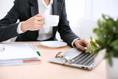 Zakończenie biznesowej kobiety ręki z filiżanką kawy up pisać na maszynie na laptopie w i Fotografia Stock