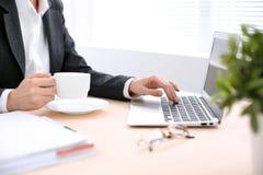 Zakończenie biznesowej kobiety ręki z filiżanką kawy up pisać na maszynie na laptopie w i Zdjęcia Stock