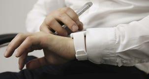 Zakończenie biznesowy mężczyzna w białej koszula robi gestom na noszonym smartwatch komputeru przyrządzie zbiory