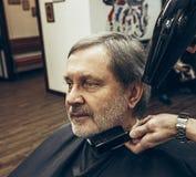 Zakończenie bocznego widoku portret przystojny starszy brodaty caucasian mężczyzna dostaje brodę przygotowywa w nowożytnym zakład Fotografia Stock