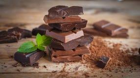 Zakończenie brogująca ciemna i dojna czekolada z świeżą mennicą na drewnianym tle, obraz stock