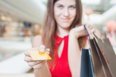 Zakończenie caucasian kobiety ręka trzyma kredytową kartę i torby Zdjęcia Royalty Free