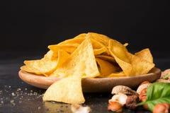 Zakończenie crispy nachos na lekki drewniany round talerz Kukurydzani układy scaleni obok nutsand basilu opuszczają na czarnym tl Zdjęcia Stock
