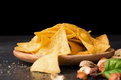 Zakończenie crispy nachos na lekkim drewnianym round talerzu Kukurydzani układy scaleni obok dokrętek i basilów liści na czarnym  Obrazy Stock
