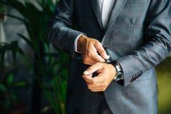 Zakończenie cropped rama elegancki nikły mężczyzna w kurtki spojrzeniach przy jego zegarek Biznesmen ogląda czas fotografia royalty free
