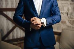 Zakończenie cropped rama mężczyzna stawia dalej złocistego zegarek z rzemiennym paskiem, ubiera w eleganckim kostiumu, biel obrazy royalty free
