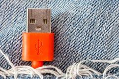 Zakończenie czerwony USB kabel w cajgach wkładać do kieszeni Fotografia Stock