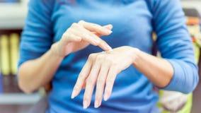 Zakończenie dla ciężkiej pięknej kobiety stosuje na ręka kosmetyka crea Obraz Stock