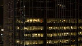 Zakończenie dla w górę drapacz chmur okno jarzy się przy nocą i ludźmi wśrodku, nocy życia pojęcie zapas Zamyka w górę nowożytneg zdjęcie royalty free
