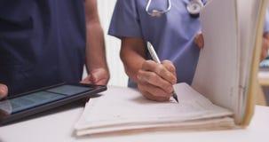 Zakończenie dojrzały żeński pielęgniarki writing w pacjenta falcówce fotografia royalty free
