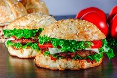 Zakończenie dom zrobił smakowitym hamburgerom na drewnianym stole Obraz Stock