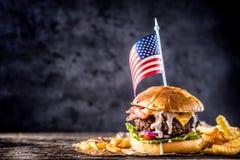 Zakończenie dom zrobił wołowina hamburgerowi z flaga amerykańską i dłoniakami na w Zdjęcie Stock