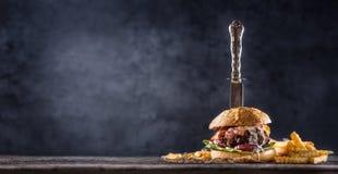Zakończenie dom zrobił wołowina hamburgerowi z nożem i dłoniakami na drewnianym ta Obrazy Stock