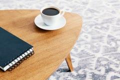 Zakończenie drewniany stół z ślimakowatym notepad i filiżanką kawy z rozmytym tłem wzorzysty dywanik Istna fotografia obrazy stock
