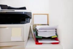 Zakończenie drukarka i papierkowa robota w prawdziwego życia biurze Zdjęcie Stock