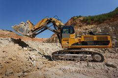 Zakończenie duży żółty ekskawator na nowej budowy miejscu na piaskowatym łupu tle i niebieskim niebie Fotografia Royalty Free