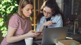 Zakończenie dwa żeńskiego ucznia używa mądrze telefon Atrakcyjna blond dziewczyna dotyka ekran i gawędzi z jej przyjacielem zbiory