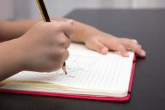 Zakończenie dzieci wręcza writing na ćwiczenie książce Zdjęcia Royalty Free
