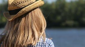 Zakończenie dziewczyna w słomianego kapeluszu spojrzeniach przy rzeką zdjęcie wideo