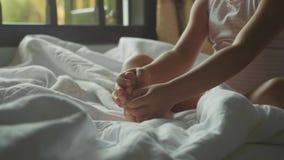 Zakończenie dziewczynka siedzi na macaniu i łóżku jej stopa w zwolnionym tempie zdjęcie wideo