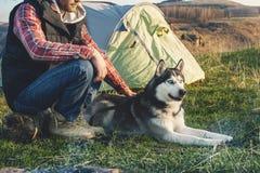 Zakończenie facet brodaty w cajg w kratkę koszula i sleeveless kurtce z psią plewą na urlopowym obsiadaniu na naturze następnie Fotografia Stock