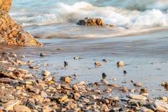 Zakończenie fala na rzeki plaży z pomarańczowym piaskiem zdjęcie stock