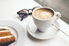 Zakończenie filiżanka kawy i tort na białym stole Zdjęcie Royalty Free