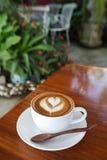 Zakończenie filiżanka latte kawa na drewnianym (Selekcyjna ostrość) obrazy stock