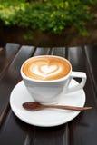Zakończenie filiżanka latte kawa na drewnianym (Selekcyjna ostrość) obraz stock