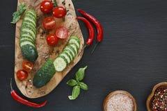 Zakończenie fotografia świezi warzywa na drewnianej tnącej desce z nożem na czerń betonującym stołowym tle Odgórny widok Obraz Royalty Free