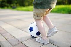Zakończenie fotografia chłopiec ma zabawę bawić się mecz piłkarskiego na pogodnym letnim dniu Zdjęcia Royalty Free