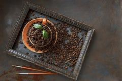 Zakończenie fotografia filiżanka z aromat kawowymi fasolami i świeżą zielenią opuszcza w ramie na czerń stołu tle Obraz Stock