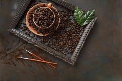 Zakończenie fotografia filiżanka z aromat kawowymi fasolami le i świeżą zielenią Zdjęcie Stock