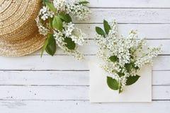 Zakończenie fotografia kapeluszowa pobliska koperta z pięknymi kwiatonośnymi gałąź na białym drewnianym tle Obrazy Stock