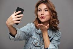 Zakończenie fotografia młody atrakcyjny kobiety dosłania powietrza buziak podczas gdy zdjęcia stock