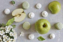 Zakończenie fotografia macaroons, zielony jabłko i piękni świezi kwiaty na popielatym stołowym tle, Obrazy Royalty Free
