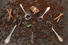 Zakończenie fotografia metal łyżki z aromat kawowymi fasolami i świeży Zdjęcie Stock