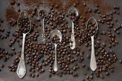 Zakończenie fotografia metal łyżki z aromat kawowymi fasolami na czerni Zdjęcia Stock