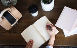 Zakończenie fotografia scheduler notatnik na drewnianym stole Żeńska ręka pisze na papierze Fotografia Royalty Free