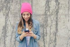 Zakończenie fotografia uśmiechniętej modniś dziewczyny czytelniczy tekst na smartphone Jest bardzo szczęśliwa ponieważ dostać zap zdjęcie stock