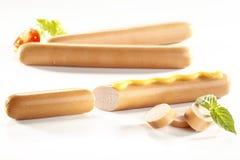 Zakończenie frankfurter kiełbasy, weenies z musztardą na bielu zdjęcia stock