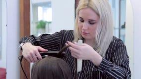 Zakończenie fryzjer używa fryzowań żelaza dla włosy tworzyć kędziory zdjęcie wideo